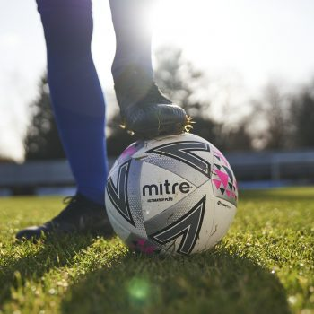 mitre football, man with foot on ball, ball on grass pitch